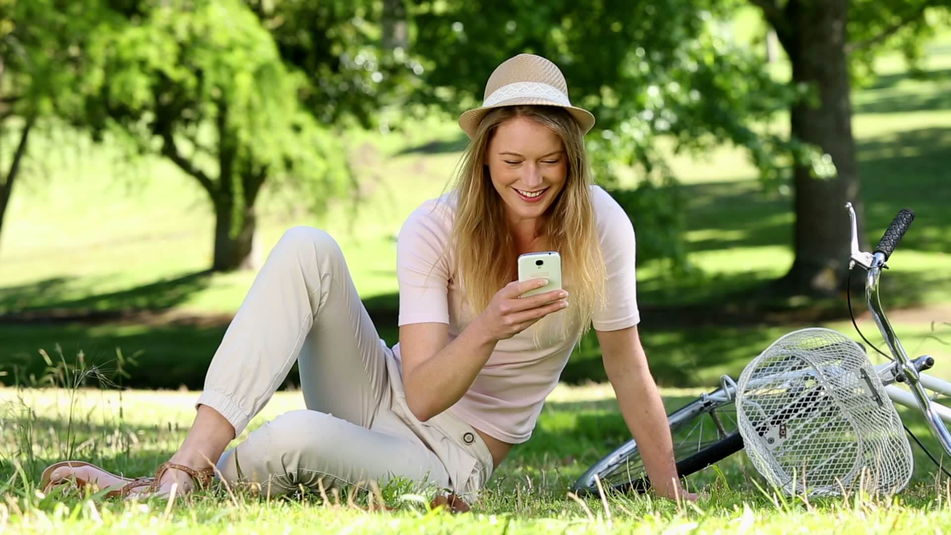 stock-footage-pretty-girl-using-smartphone-beside-her-bike-in-the-park-on-a-sunny-day.jpg